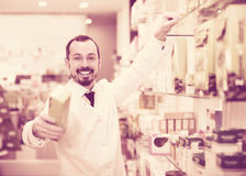 Smiling man pharmacist offering right drug. In  drugstore Royalty Free Stock Photos
