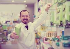 Smiling man pharmacist offering right drug. In  drugstore Stock Photos