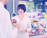Smiling man pharmacist wearing uniform assisting customers Stock Image
