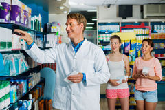 Smiling man pharmacist  working in pharmaceutical shop Royalty Free Stock Photo