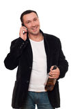 Smiling man with a phone and bottle of scotch Royalty Free Stock Images