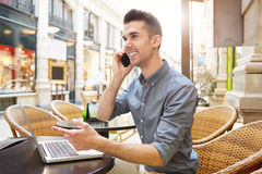 Smiling man on phone call at outside cafe with laptop Royalty Free Stock Images