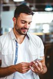 Smiling man on the phone having coffee Royalty Free Stock Image