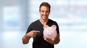 Smiling man with piggy bank. Stock Images