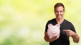 Smiling man with piggy bank. Royalty Free Stock Image