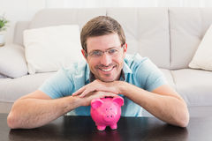 Smiling man with a piggy bank Stock Image