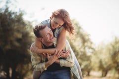 Smiling man piggybacking woman at olive farm Royalty Free Stock Photo