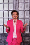 Smiling man in pink suit stands against old icy door stock image