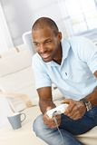 Smiling man playing computer game Stock Images