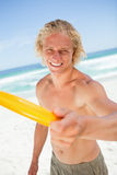 Smiling man playing frisbee while standing on the beach. Smiling man holding a yellow frisbee while standing on the beach Stock Images