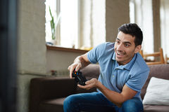 Smiling Man Playing Video Games. Portrait of handsome emotional adult man playing video game holding wireless controller and  smiling joyfully while sitting on Stock Images