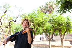 Smiling man playing violin outside Royalty Free Stock Images