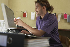 Smiling Man Pointing At Computer Screen In Office Royalty Free Stock Photography