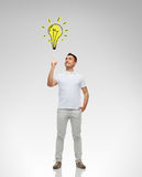 Smiling man pointing finger to lighting bulb. Happiness, gesture and people concept - smiling man pointing finger up to lighting bulb doodle over gray background royalty free stock photography