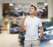 Smiling man pointing finger up over auto show Royalty Free Stock Photo
