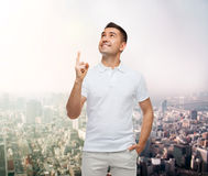 Smiling man pointing finger up over city Royalty Free Stock Photography