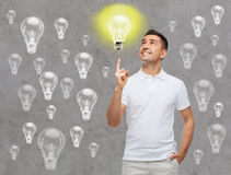 Smiling man pointing finger up to lighting bulb Royalty Free Stock Photography