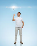 Smiling man pointing finger up to lighting bulb. Happiness, gesture and people concept - smiling man pointing finger up to lighting bulb over blue background stock images