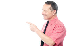 Smiling man pointing his finger towards something Royalty Free Stock Images