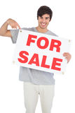 Smiling man pointing at for sale sign Stock Photos