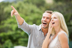 Smiling man pointing while standing by surprised woman Royalty Free Stock Photo