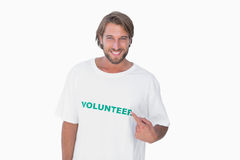 Smiling man pointing to his volunteer tshirt Royalty Free Stock Photography