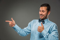 Smiling man pointing to something with an index finger Royalty Free Stock Photos