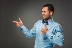 Smiling man pointing to something with an index finger Royalty Free Stock Images