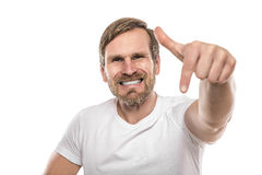 Smiling man points down to an empty space. Stock Images