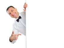 Smiling man points a finger at to do list. Smiling man in a white shirt and bow tie points a finger at to do list Royalty Free Stock Photo
