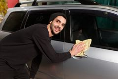 A smiling man is polishing a car royalty free stock image