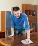 Smiling man polishing table with furniture polish Stock Photos