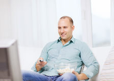 Smiling man with popcorn watching movie at home Stock Photos