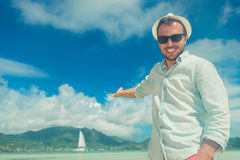 Smiling man presenting from a boat on the exotic sea Stock Photo
