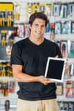 Smiling Man Presenting Digital Tablet In Hardware Royalty Free Stock Photos