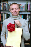 Smiling man presenting a gift with flower Stock Photo