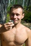 Smiling man proposing a toast. Young smiling man proposing a toast in a forest Stock Photography