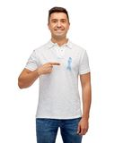 Smiling man with prostate cancer awareness ribbon. Medicine, health care, gesture and people concept - smiling middle aged latin man in t-shirt with blue royalty free stock photography