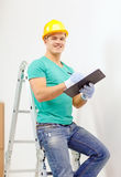 Smiling man in protective helmet with clipboard Royalty Free Stock Photography