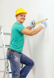 Smiling man in protective helmet measuring wall. Repair, building and home concept - smiling man in yellow protective helmet measuring wall Royalty Free Stock Image
