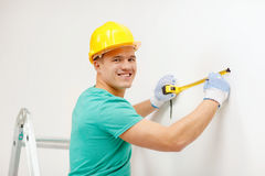Smiling man in protective helmet measuring wall. Repair, building and home concept - smiling man in yellow protective helmet measuring wall Stock Photo