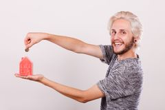 Smiling man putting coin into house piggybank Stock Photos