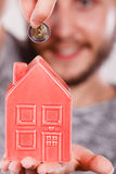 Smiling man putting coin into house piggybank Royalty Free Stock Images
