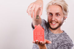 Smiling man putting coin into house piggybank Royalty Free Stock Photography