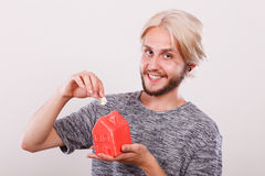 Smiling man putting coin into house piggybank Royalty Free Stock Image