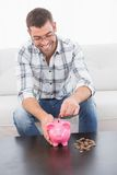 Smiling man putting coins in a piggy bank Royalty Free Stock Images