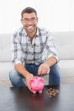 A smiling man putting coins in a piggy bank Stock Photo