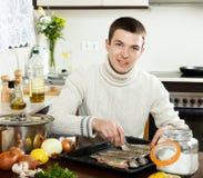 Smiling man putting  saltwater fish into sheet pan Royalty Free Stock Photo