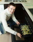 Smiling man putting trout fish  into oven Royalty Free Stock Photo