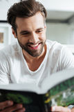 Smiling man reading book. Looking aside. Royalty Free Stock Images